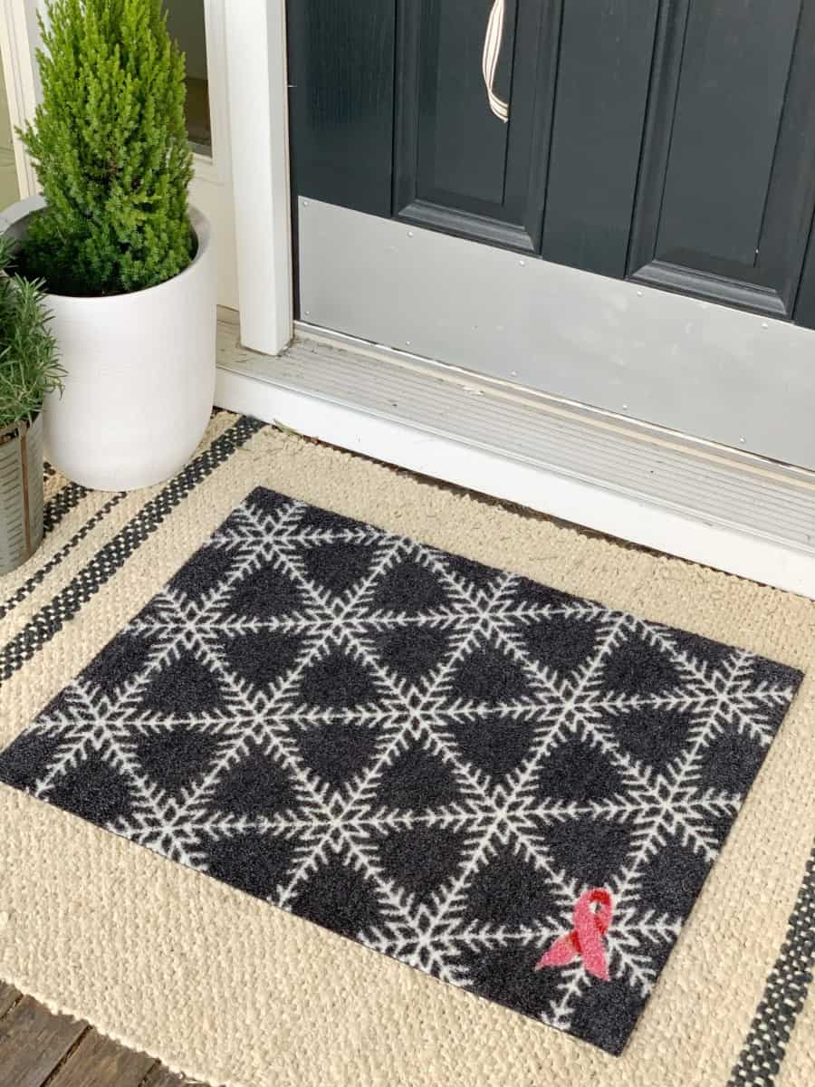 Front porch Christmas decor featuring a welcome mat for breast cancer research.