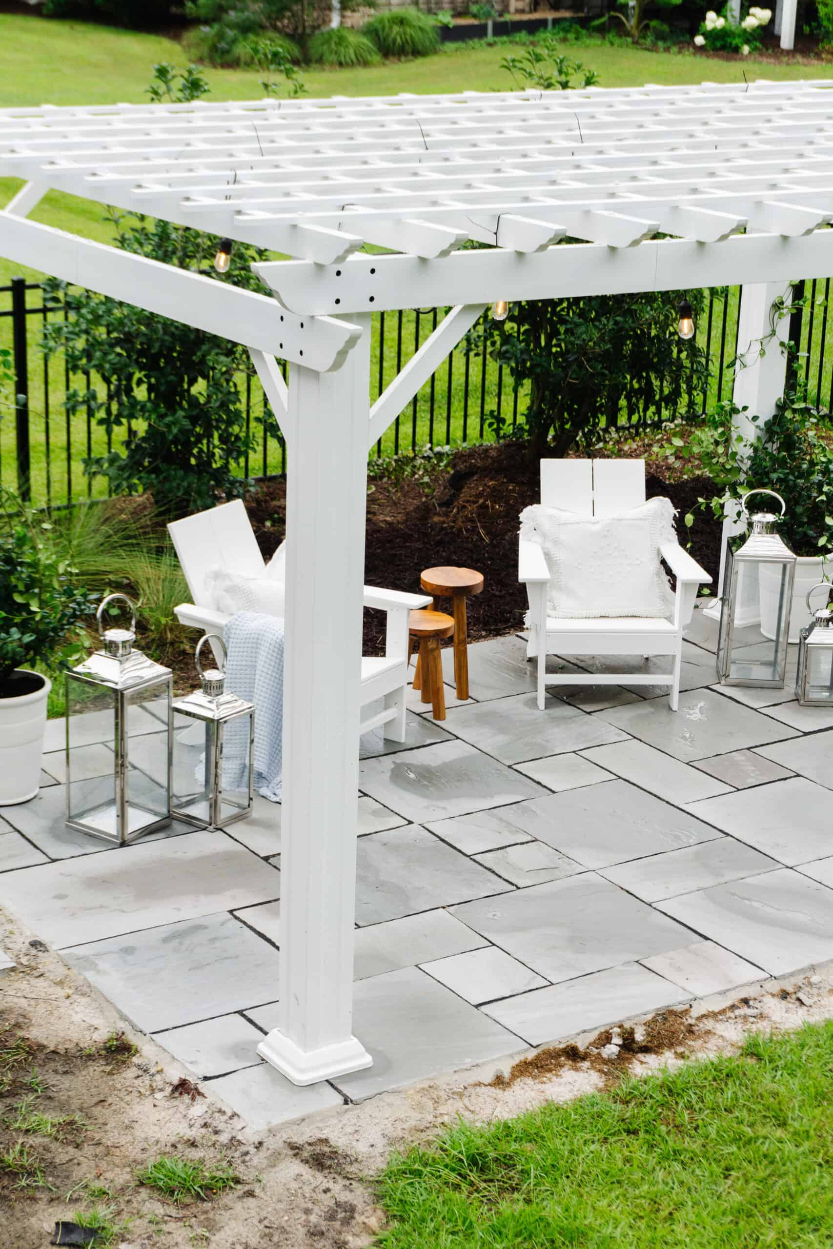 Patio with white pergola and two Adirondack chairs.