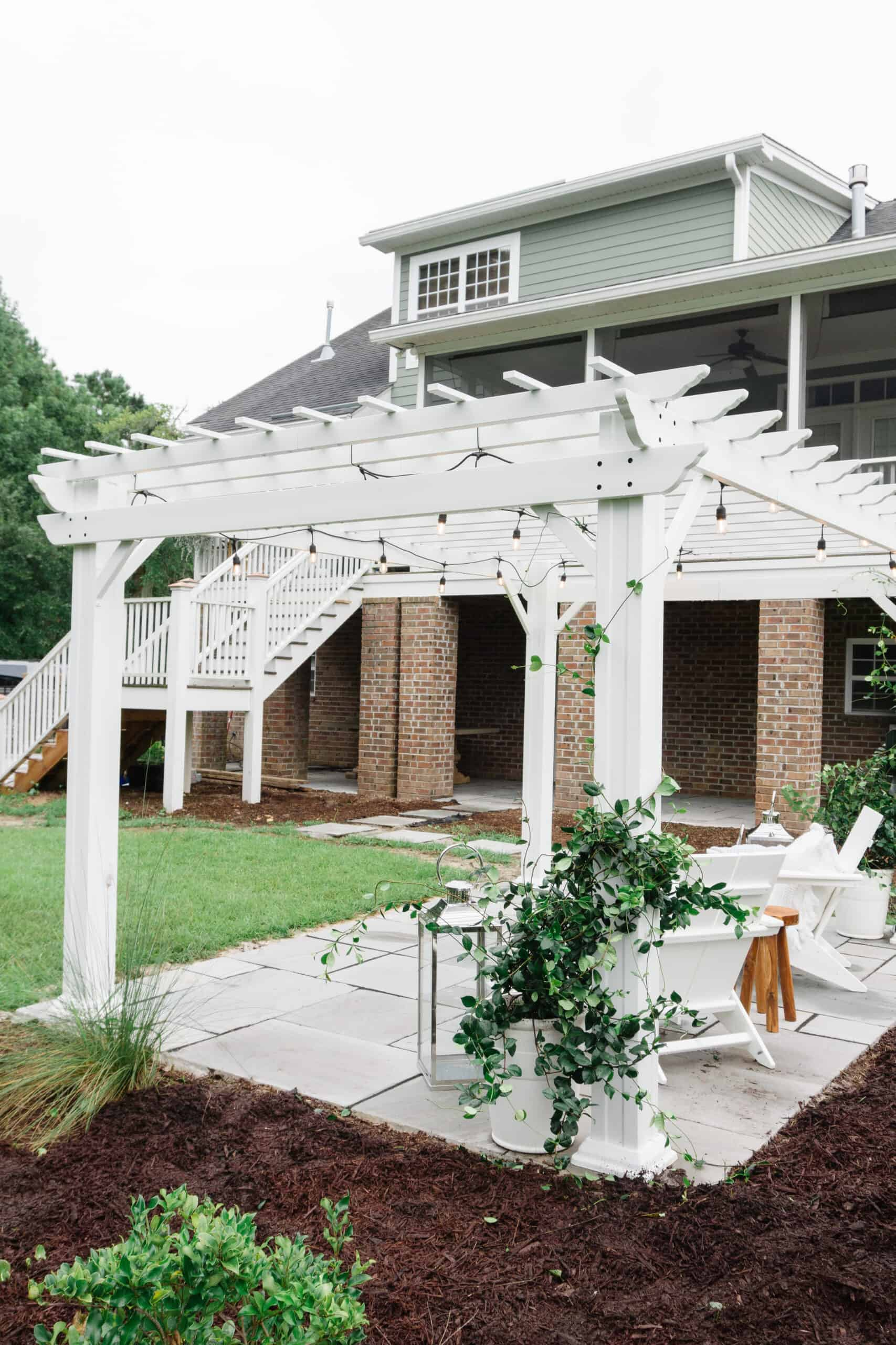 White pergola with lights behind house.