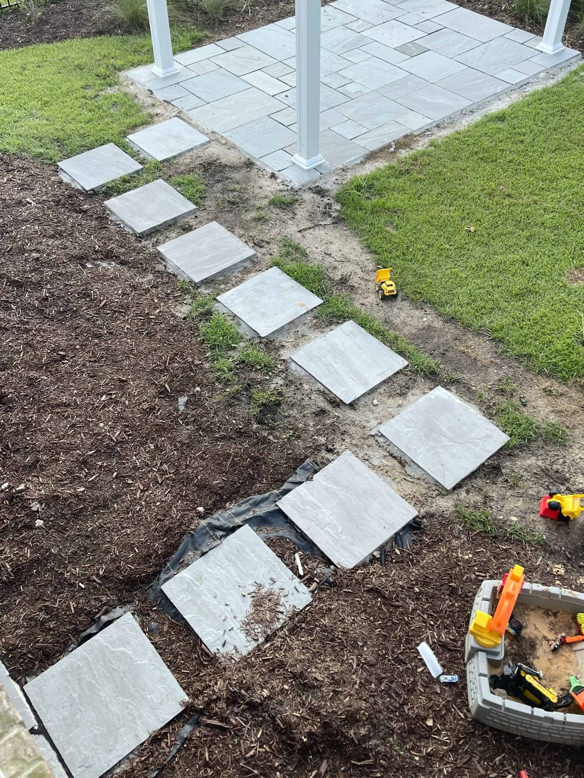 Stepping stones on top of grass leading to white pergola and patio.