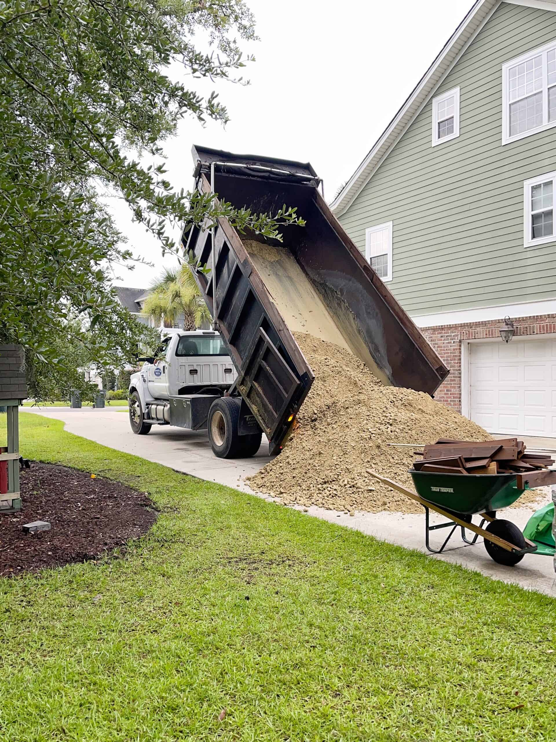 Dump druck in driveway delivering compact material and sand.