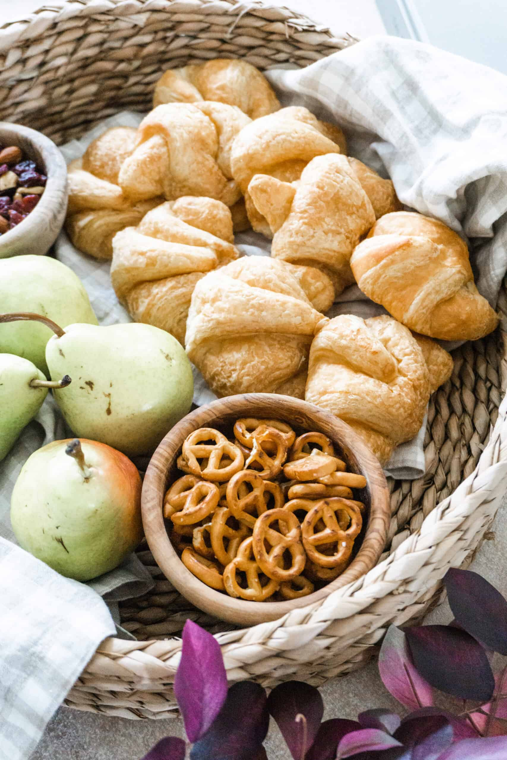 Basket tray styled with croissants and pears.
