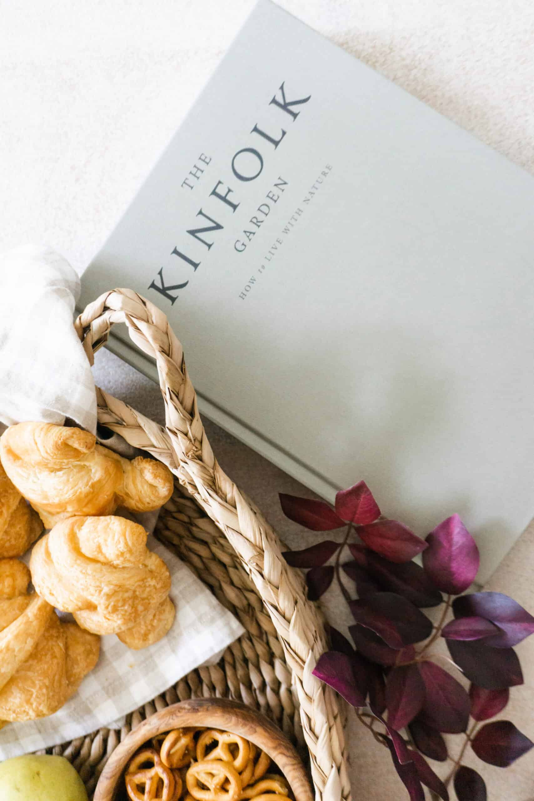 Kinfolk garden book with walmart basket styled with croissants and fruit.