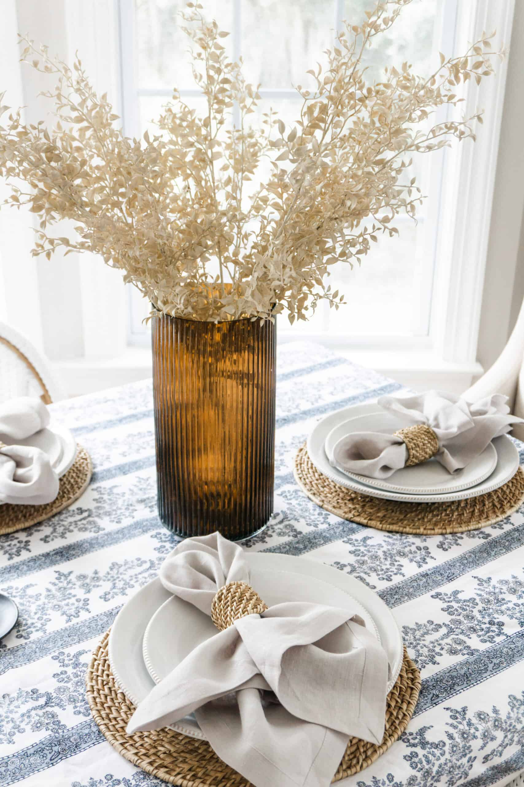 Natural stems placed in an amber vase as a centerpiece.