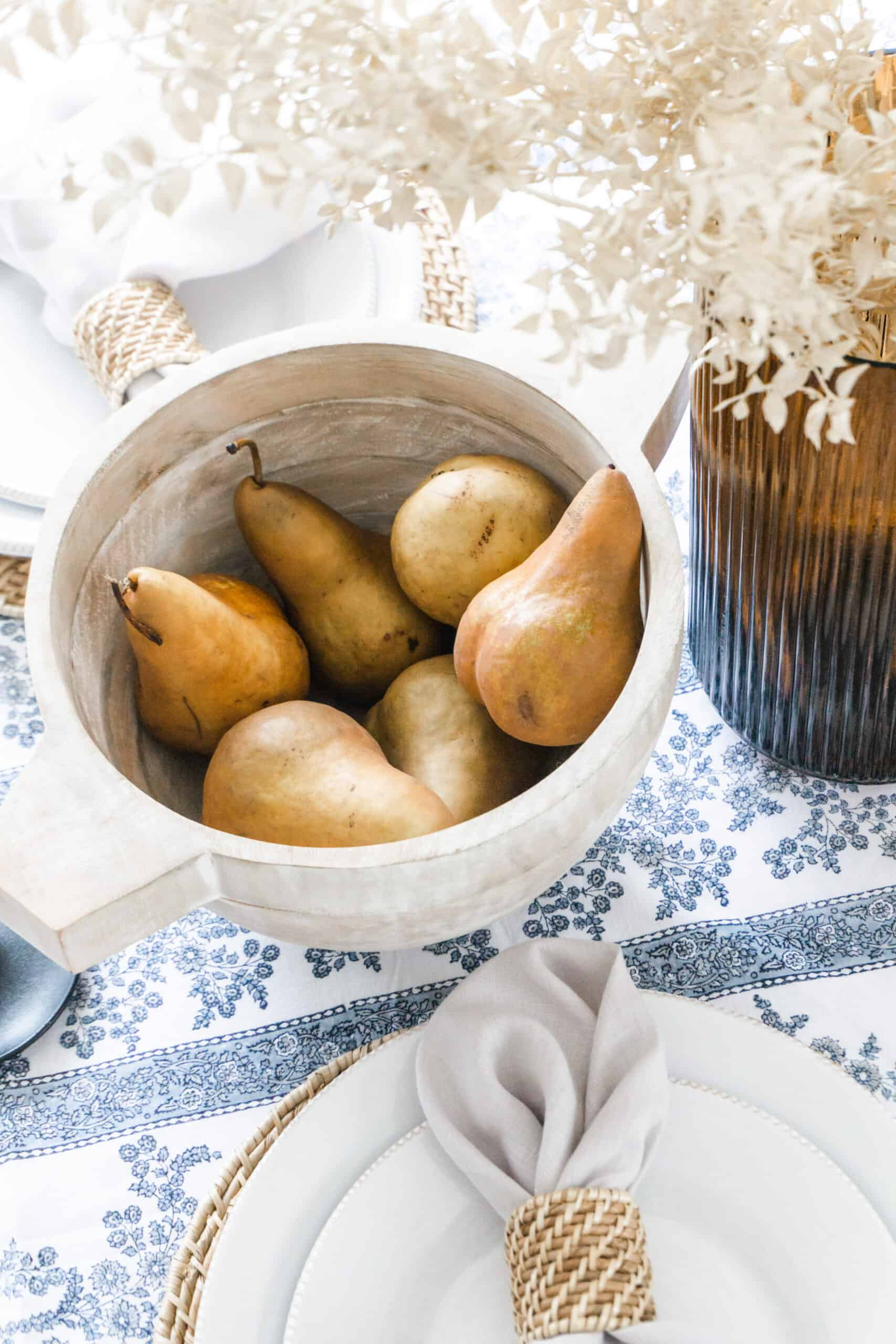 Pears in bowl as a centerpiece on top of blue floral tablecloth.