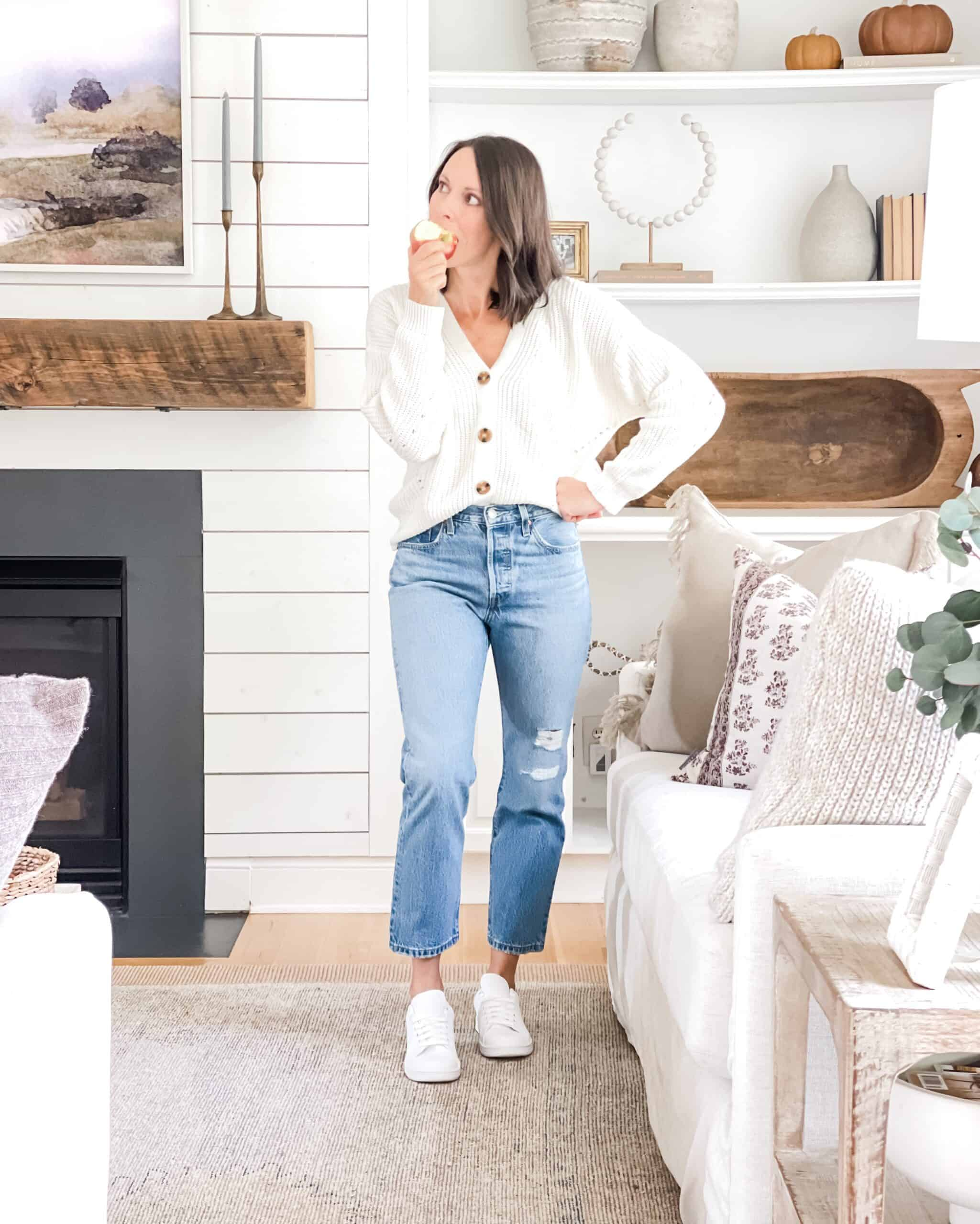 White walmart button up sweater and high rise jeans in front of fireplace.